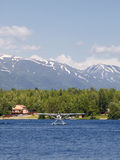 Float plane on Seymore lake. Scenic view of float plane on Seymore lake with snow capped mountains in background, Alaska, U.S.A Stock Image