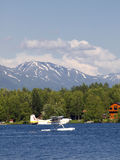 Float plane on Seymore lake. Scenic view of float or pontoon plan on Seymore lake with snow capped mountains in background, Alaska, U.S.A Stock Photo