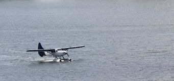Float Plane on Water. A blue and white float plane is motoring on the water. The water is calm. The plane is in the bottom left third of the picture Royalty Free Stock Photography
