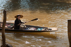 Floating asian vendors on long wooden boat Royalty Free Stock Photos