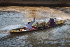 Floating asian vendors on long wooden boat Royalty Free Stock Images