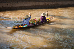 Floating asian vendors on long wooden boat stock photos
