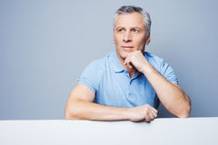 Floating away at his thoughts. Handsome senior man holding hand on chin and leaning at copy space while standing against grey background Royalty Free Stock Photos