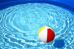 Floating ball in a swimming pool. A colorful ball floating in a sparkling swimming pool Royalty Free Stock Images