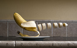 Floating Banana. Banana floating over a plate chopped up over a kitchen counter top Royalty Free Stock Photo