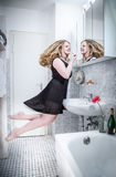 Floating in the bathroom. Women gets ready to go out and floats in front of the mirror Royalty Free Stock Photo