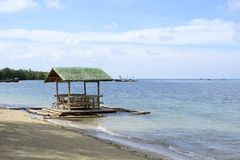 Floating beach bamboo and palm cottage parasol on white sand coast Stock Photos