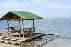 Floating beach bamboo and palm cottage parasol on white sand coast Royalty Free Stock Images