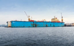 Floating blue dry dock with red tanker under repair Stock Photos