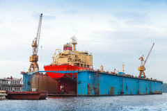 Floating blue dry dock with red tanker under repair Stock Images