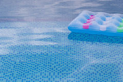 Floating blue and pink air mattress  swimming pool Royalty Free Stock Photo