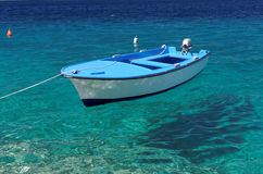 Floating boat on crystal sea Royalty Free Stock Photography