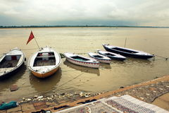 Floating boats and saris in Varanasi. Boats on the Ganges and sari drying on the riverside Royalty Free Stock Images
