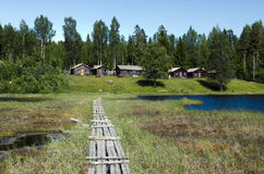 Floating bridge. Old bridge from 1898 built on floating moss over a lake in the North of Sweden and in the background some old timbered house Stock Photo