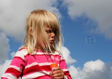 Floating bubble. A little girl playing in the summer sun blowing bubbles, semi clear blue sky in background Stock Photo