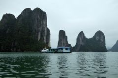 Floating building surrounded by the dramatic islands of ha long bay Vietnam Royalty Free Stock Image