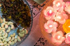 Floating candles and dry fruits. Glass bowl filled with flower shaped floating candles and a glass try with dry fruits like cashew nuts, raisins. This is the Stock Photos