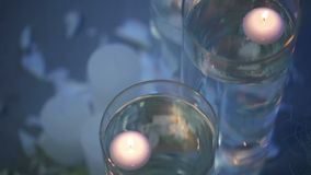 Floating candles. Two Candles floating in water in glass flasks stock video footage