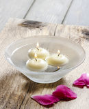 Floating candles in water among rose petals Royalty Free Stock Photos