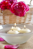 Floating candles in water among rose petals Royalty Free Stock Image