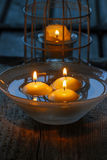 Floating candles in water among rose petals Royalty Free Stock Images