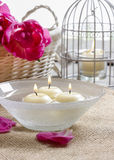 Floating candles in water among rose petals Stock Photo
