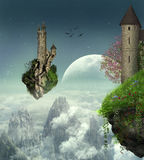Floating castles. Two floating islands with their castles are surfing the sky over the mountains and clouds Royalty Free Stock Photography