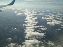 Floating on clouds. Line of clouds above land through a plane window royalty free stock photography