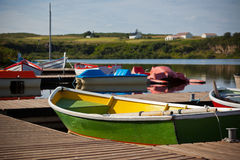 Floating Color Wooden Boats with Paddles in a Lake Stock Photos