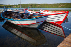 Floating Color Wooden Boats with Paddles in a Lake Stock Images