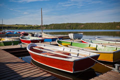 Floating Color Wooden Boats with Paddles in a Lake Stock Photo