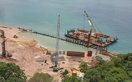 Floating construction platform. Arial view of a floating construction platform building a dam stock images