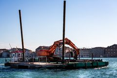 Floating crane with wooden pilings needed to maintain the canals in Venice, Italy stock photography