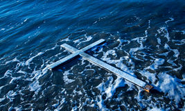 Floating Cross. White cross floating on water with some white sea foam around it Stock Photo