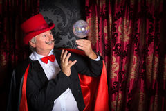 Floating crystal ball and magician. Senior magician performing on stage with a crystal ball Royalty Free Stock Photo