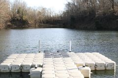 Floating Dock at a Lake. A floating dock that extends out into a river for fishing and paddle boat rides royalty free stock images