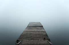 Floating dock in mist. Wooden floating dock in misty lake Stock Photos
