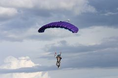 Floating down. Parachute in front of clouds stock photos