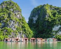 Floating fishing village, Ha Long bay, Vietnam. Floating fishing village with rock island in background, Ha Long bay, Vietnam Royalty Free Stock Image