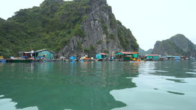 Floating fishing village. And rock islands in Halong Bay, Vietnam, Southeast Asia. Vietnamese live in houses floating on the water. 4K stock footage