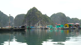 Floating fishing village. And rock islands in Halong Bay, Vietnam, Southeast Asia. Vietnamese live in houses floating on the water. 4K stock video footage