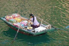 Floating food seller with baby in Halong Bay Stock Photo
