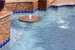 Floating fountain within a swimming pool Stock Photo
