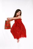 Floating Gift. Pretty little girl in red dress floating with Christmas gift Royalty Free Stock Photos