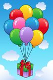 Floating gift with cartoon balloons Royalty Free Stock Photo
