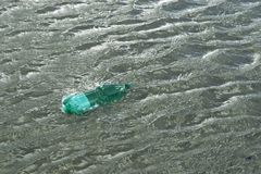 Floating green bottle Royalty Free Stock Photography