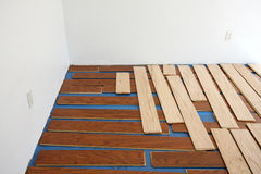 Floating hardwood floor installation. Strips of wood laid out on a concrete floor before being snapped together making a hardwood floor Royalty Free Stock Photos