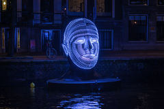 Floating head made of lights in an Amsterdam canal. Stock Image