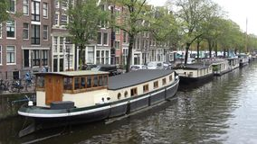 A floating home, moored on the Prinsengracht canal. Amsterdam stock video footage