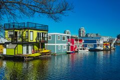 Floating Home Village colorful Houseboats Water Taxi Fisherman`s Wharf Reflection Inner Harbor, Victoria British Columbia Canada. Pacific Northwest. Area has royalty free stock photo